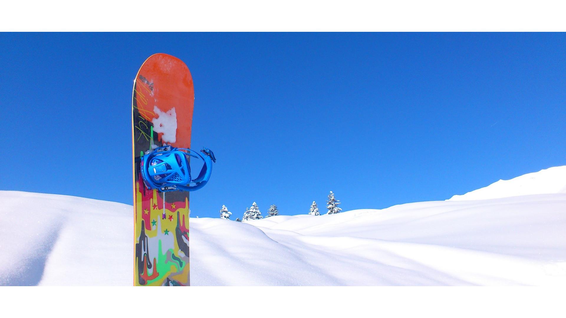 kara saplanmış snowboard görseli.